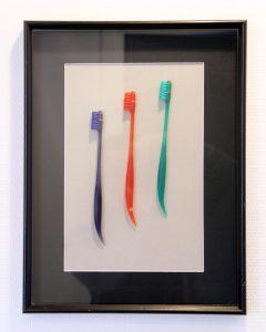 Tandborstar i olika färger uppsatta i en tavla.